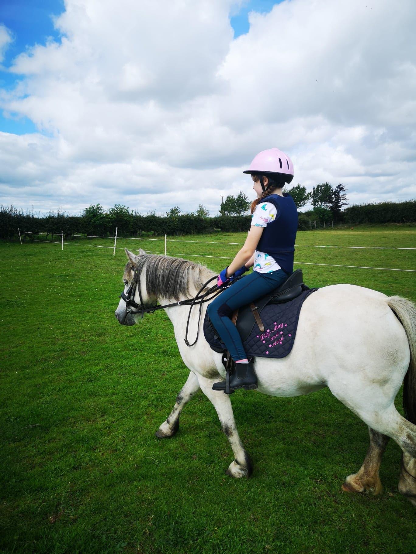 Girl riding a white pony