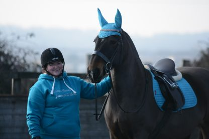 lady in a blue hoodie with her horse