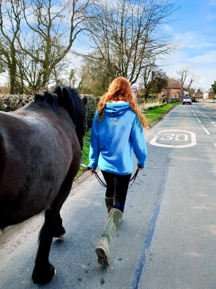 Girl in blue eventing hoodie walking her horse