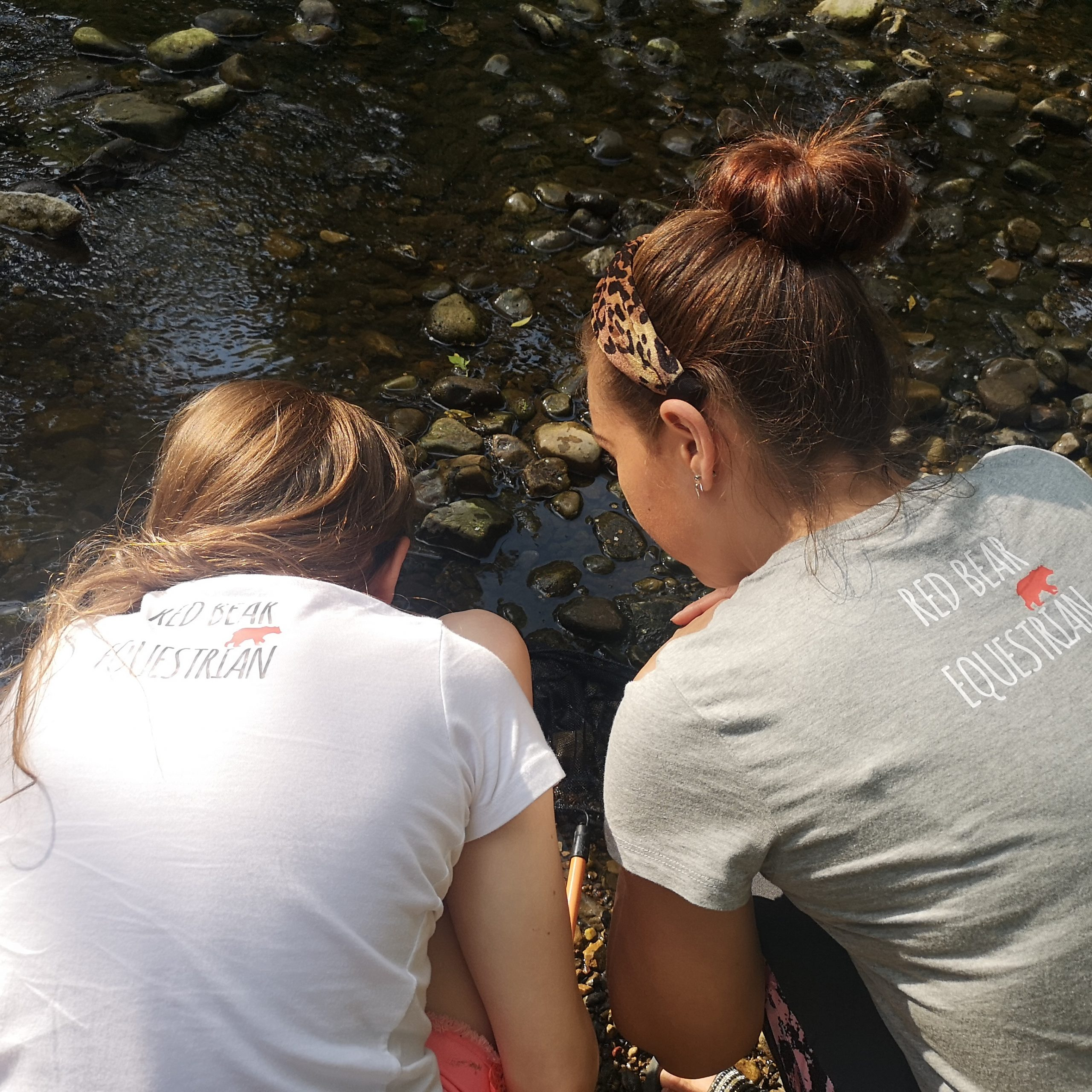 lady and child in red bear equestrian t shirts by the river