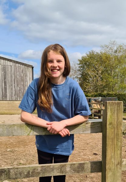 girl in blue t-shirt stood at a fence