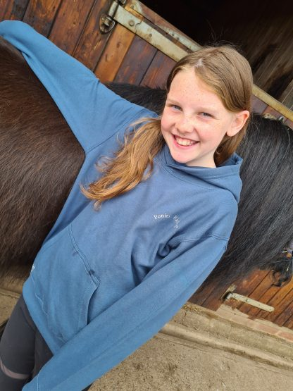 girl in blue hoodie with horse