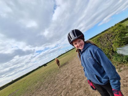 girl in blue hoodie and riding hat