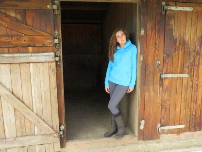 Lady in blue hoodie stood in stable